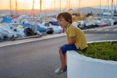 Sött litet barn, litet barnpojke som sitter och håller ögonen på hamnen royaltyfri foto