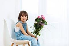 Sött litet barn, pojke och att sitta på en stol hemma och att rymma flo arkivfoton