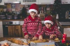 Sött litet barnbarn och hans äldre broder, pojkar, hjälpande mamma som hemma förbereder julkakor arkivbild