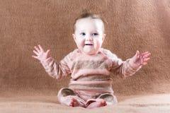 Sött lyckligt behandla som ett barn flickan på en brun filt Royaltyfri Bild