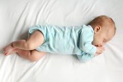Sött nyfött behandla som ett barn att sova på vit säng Royaltyfria Bilder