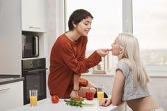 Sött och gulligt sköt inomhus av den varma skjorta-haired kvinnan som matar hennes flickvän, medan sitta på köksbordet och förber royaltyfri fotografi