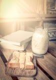 Sött rostat bröd med mjölkar i krus på trätabellen med böcker Royaltyfri Fotografi