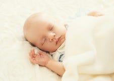 Sött sömnspädbarn på sängen Fotografering för Bildbyråer