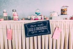 Sött stångpapperstecken på brölloptabellen med färgade sötsaker royaltyfri foto