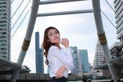 Sûr et avec du charme Portrait de la jeune femme asiatique touchant son menton avec des doigts au fond urbain de bâtiment Photographie stock