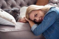 Süße blonde Dame mit ihrer Katze auf Couch Lizenzfreies Stockbild