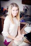 Süße blonde Frau der Junge recht bereitet Teig in der Küchenglücklichen lächelnden u. schauenden Kamera zu Lizenzfreie Stockbilder