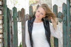 Süße blonde Frau, die an einem Zaun sich lehnt Lizenzfreie Stockfotos