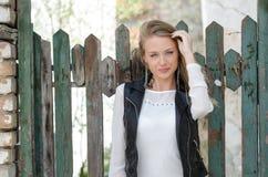 Süße blonde Frau, die an einem Zaun sich lehnt Stockbilder