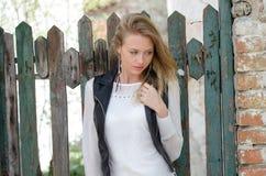 Süße blonde Frau, die an einem Zaun sich lehnt Stockbild