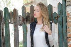 Süße blonde Frau, die an einem Zaun sich lehnt Lizenzfreie Stockbilder