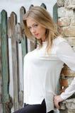 Süße blonde Frau, die an einem Zaun sich lehnt Lizenzfreie Stockfotografie
