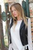 Süße blonde Frau, die an einem Zaun sich lehnt Lizenzfreies Stockfoto