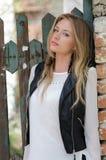 Süße blonde Frau, die an einem Zaun sich lehnt Stockfoto