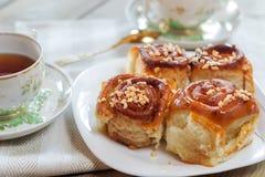 Süße Brötchen mit Zimt, Nüssen und Karamelsirup Lizenzfreie Stockfotos