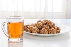 Süße Erdnussbälle in einer Platte und in einem Glas schwarzem Tee Stockfotos