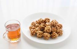 Süße Erdnussbälle in einer Platte und in einem Glas schwarzem Tee Stockfotografie