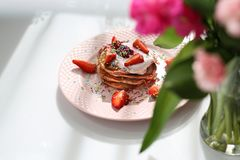 Süße Frühstück Rosapfannkuchen mit Erdbeeren, Hüttenkäse und buntem Zucker besprüht stockfotografie