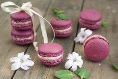 Süße hochrote französische Makronen mit Hyazinthenblumen und -minze auf dunklem hölzernem Hintergrund Stockfotos