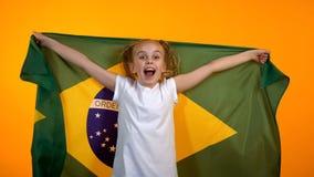 Süße Jugendliche, die für brasilianisches Lieblingsteam, Staatsflagge halten zujubelt lizenzfreie stockfotografie