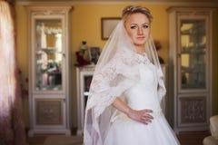 Süße junge blonde Braut, die im stilvollen Hochzeitskleid auf einem Ba aufwirft Lizenzfreie Stockbilder
