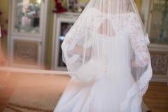 Süße junge blonde Braut, die im stilvollen Hochzeitskleid auf einem Ba aufwirft Stockfotografie
