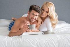 Süße junge kaukasische Liebhaber auf dem Bett, das Kaffee trinkt Stockbild