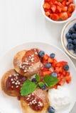 süße Käsepfannkuchen mit frischen Beeren und Creme auf Weiß Stockbilder