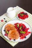 Süße Käsepfannkuchen mit frischen Beeren und Milch Lizenzfreies Stockfoto