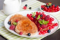 Süße Käsepfannkuchen mit frischen Beeren und Milch Stockfotografie