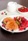 Süße Käsepfannkuchen mit frischen Beeren und Milch Stockfoto