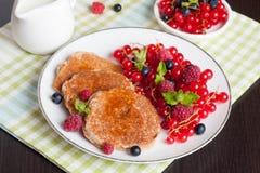 Süße Käsepfannkuchen mit frischen Beeren und Milch Lizenzfreie Stockfotografie