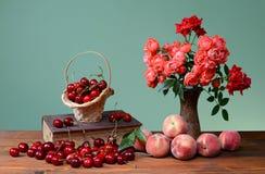 Süße Kirschen, Bücher und Blumen in einem Vase Lizenzfreie Stockbilder