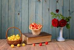 Süße Kirschen, Bücher und Blumen in einem Vase Stockfoto