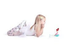 Süße kleine Ballerina, die mit ihrer Puppe aufwirft Stockfotos