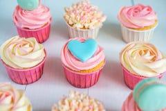 Süße kleine Kuchen mit Sahne, verzierter Lebkuchen, Perlen und makarons für leichtes raffiniertes Mädchen oder eine kleine Prinze Stockfotos
