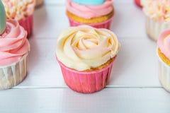 Süße kleine Kuchen mit Sahne, verzierter Lebkuchen, Perlen und makarons für leichtes raffiniertes Mädchen oder eine kleine Prinze Lizenzfreie Stockbilder
