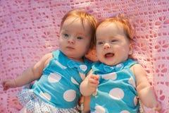 Süße kleine Zwillinge, die auf einer rosa Decke liegen Stockbilder
