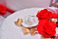 Süße Kuchen in Form von roten Rosen verzieren die Hochzeitstorte mit den dekorativeren Zweigen der weißen Creme Lizenzfreie Stockfotografie