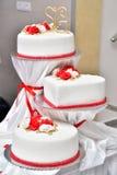 Süße Kuchen in Form von roten Rosen verzieren die Hochzeitstorte mit den dekorativeren Zweigen der weißen Creme Lizenzfreies Stockbild