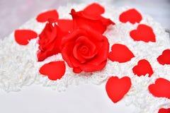 Süße Kuchen in Form von roten Rosen verzieren die Hochzeitstorte mit den dekorativeren Zweigen der weißen Creme Stockfoto