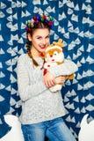Süße Mädchenstellung und -plüsch spielen auf dem Hintergrund von Weihnachten Stockbild