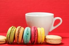 Süße macarons Kuchen der unterschiedlichen Farbe mit der Schale auf Rot gemasert Lizenzfreies Stockfoto
