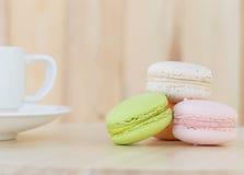 Süße Makronen, macarons mit Schale auf hölzernem Hintergrund Stockbild