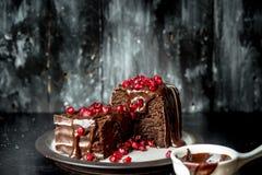 Süße Momente - Schokoladenkuchen gossen heiße, flüssige Schokolade und besprüht mit roten Granatapfelsamen lizenzfreie stockbilder