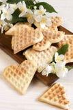 Süße Oblatenherzen auf Teller mit Blumen Stockfotos