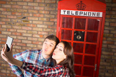 Süße Paare, die Selfie an der Telefonzelle nehmen Stockbild