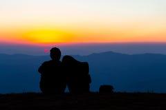 Süße Paare silhouettieren das Sitzen auf dem Berg mit Sonnenuntergang lizenzfreie stockbilder