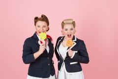 Süße Paare von Mädchen mit Lutschern Pin-oben redete Frauen mit Süßigkeiten in der Hand an Zwei süße Damen mit zwei Bonbons lizenzfreies stockfoto